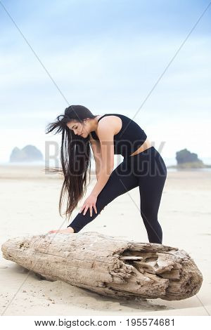 Young biracial Asian Caucasian woman in black fitness clothes doing stretches on beach by large driftwood log. Ocean in background.