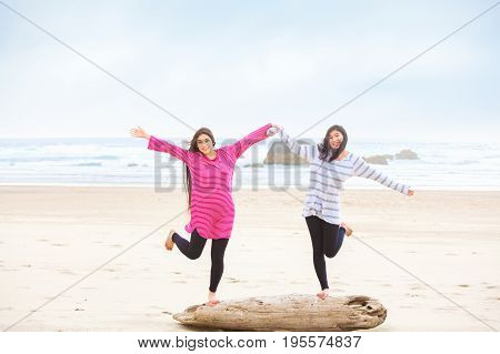 Two beautiful biracial Asian Caucasian girls standing balancing on one leg on driftwood log on beach. Ocean is in background.