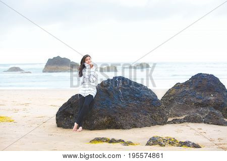 Biracial teen girl leaning barefoot against large rock on beach by ocean looking off to side thinking