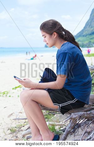 Biracial teen girl using smartphone while sitting on log at beach near ocean. Side profile.