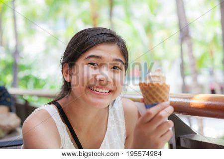 Biracial teen girl holding ice cream cone smiling