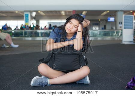 Tired or bored biracial teen girl sitting on floor at airport waiting with luggage