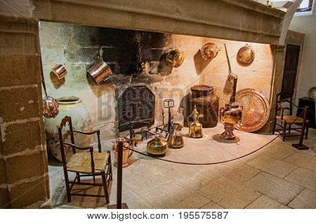 Lourmarin, France - July 07, 2016. Large stone fireplace with decorative copper kitchenware and chairs in Lourmarin castle. Vaucluse department, Provence-Alpes-Côte d'Azur region, southeastern France