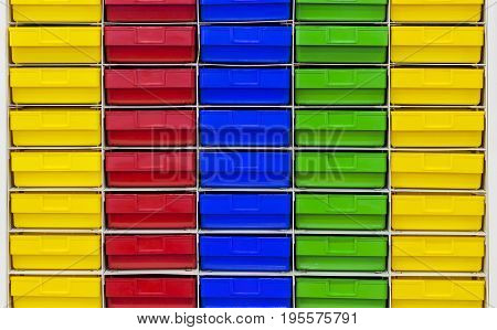 Colored plastic drawer keeping parts in workshop;storage facility