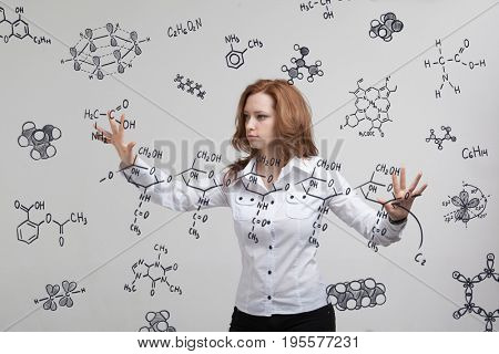 Woman chemist working with chemical formulas on grey background.