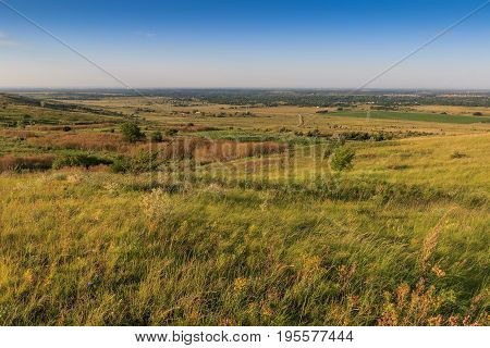 View of the settlement and the valley of the Kuban River from the hill. The hill is covered different color with a grass and bushes an atakzha rare trees.