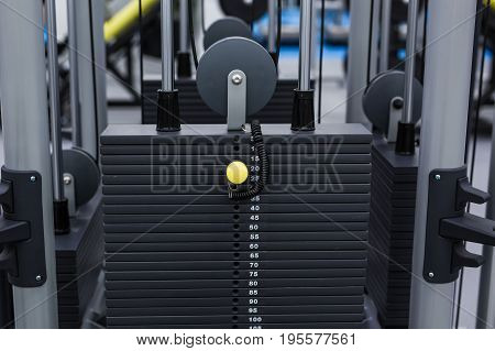 Black iron heavy plates stacked of weight machine in fitness gym. Sports simulator plates.