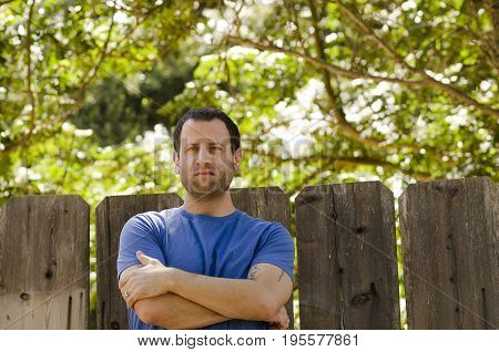 Optimistic man outdoors on a sunlight day with arms crossed looking to the left.