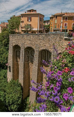 Moustiers-Sainte-Marie, France - July 08, 2016. Stone wall and houses with flowers in the lovely village of Moustiers-Sainte-Marie. Provence region, southeastern France