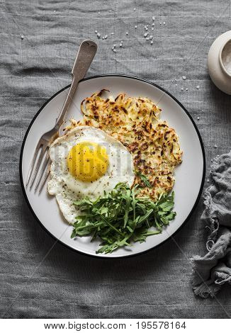 Potato latkes fried egg and arugula - delicious healthy breakfast or snack. On a gray table top view