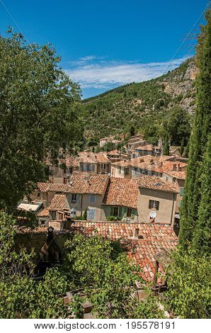 View of trees and house roofs under sunny blue sky in the charming village of Moustiers-Sainte-Marie. Located in the Alpes-de-Haute-Provence department, Provence region, southeastern France