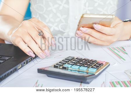 businesswoman hand holding smart phone and working on financial graph report, calculator on her desk
