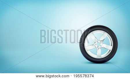 A car wheel with five spokes standing on the tire rim on blue background. Cars and transportation. Repair shop. Spares delivery.