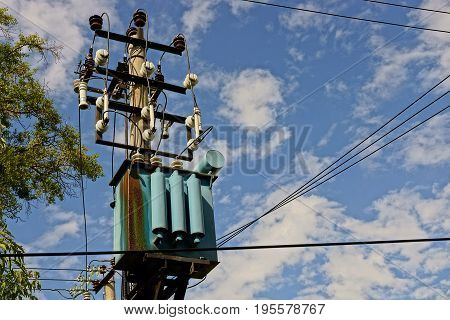 Iron rusty electrical transformer on a pole with wires