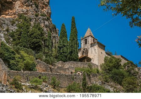 Close-up of the Notre-Dame de Beauvoir church amidst cliffs and rock stairway, above the lovely Moustiers-Sainte-Marie village. Alpes-de-Haute-Provence department, Provence region, southeastern France
