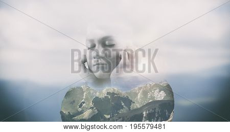 Double exposure of a thoughtful woman and a mountain landscape.