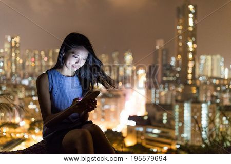 Woman looking at cellphone with the city background