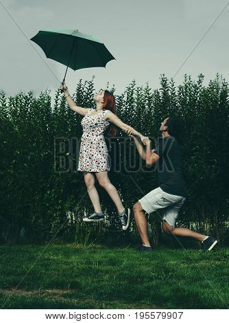 Woman taking off from the ground with an umbrella while boyfriend holds her .