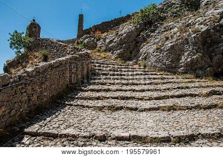 View of the staircase to the Notre-Dame de Beauvoir church, above the graceful Moustiers-Sainte-Marie village. Alpes-de-Haute-Provence department, Provence region, southeastern France