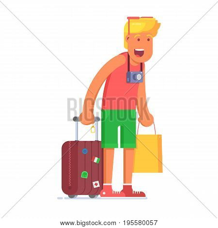 Surprised blond tourist man holding luggage and hand bag. Smiling traveler teen with suitcase and camera looking with surprise.