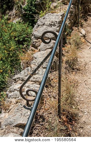 Close-up of the handrail staircase to the Notre-Dame de Beauvoir church with the village Moustiers-Sainte-Marie underneath. Alpes-de-Haute-Provence department, Provence region, southeastern France