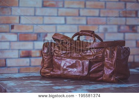 Men's accessories with Dark brown leather bags on wooden table over brick wall backgroundcolor vintage styleThailand