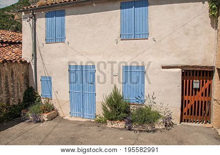 Moustiers-Sainte-Marie, France - July 08, 2016 View of house with blue shutters closed in the charming village of Moustiers-Sainte-Marie. Provence region, southeastern France