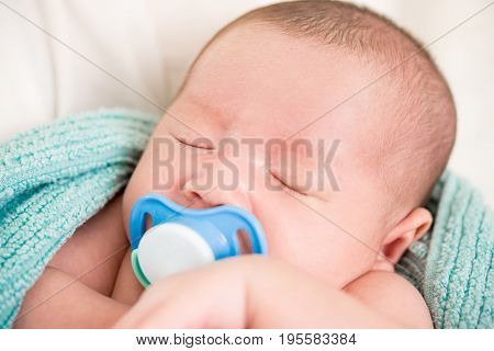 Adorable sleeping newborn baby with dummy in the mouth