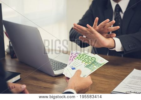Businessman rejecting money Euro banknotes from his partner while making contract - anti bribery concept