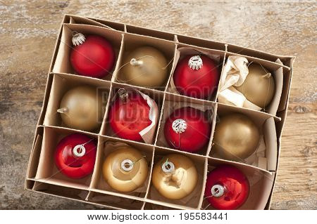 Top down view on golden colored and red christmas tree ornament balls inside cardboard box