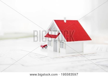 House model on blueprint paper - real estate and property concept