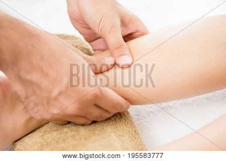 Hands of male therapist (masseur) giving massage to a woman leg