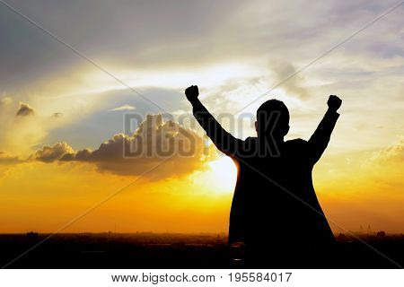 Silhouette of a man raising his arms in twilight sky background - success winning & accomplished concepts