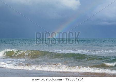 Rainbow across an overcast stormy sky and over Australian beach sea waves