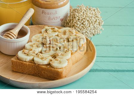Banana Peanut Butter Toast Sandwich On Wood Plate With Honey. Homemade Open Sandwich Spread With Pea