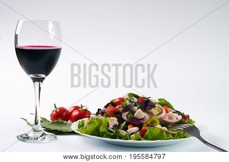 Healthy fresh vegetable salad with chicken meat next to fork and glass of red dry wine isolated on white background with copy space. Healthy eating and detox concept