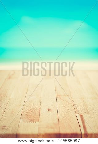 Wood table top on blur blue sea and white sand beach background summer concept vintage tone - poster size proportion