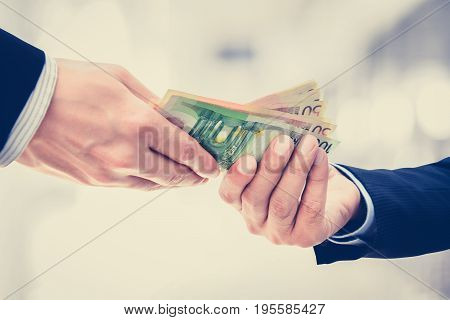 Businessman hands passing money Euro currency (EUR) on white gray background - vintage tone