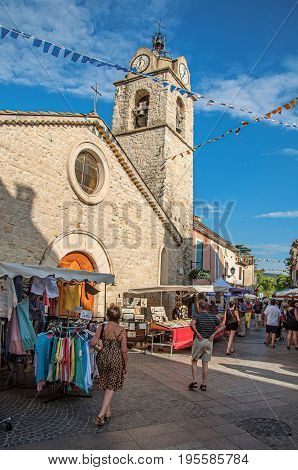 Gréoux-les-Bains, France - July 08, 2016. Church and stone street with stalls at sunset in lovely village of Gréoux-les-Bains. Alpes-de-Haute-Provence department, Provence region, southeastern France