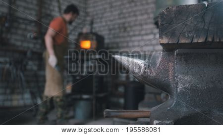 Muskular beard man blacksmith handles the item is removed from the fire, metal bends