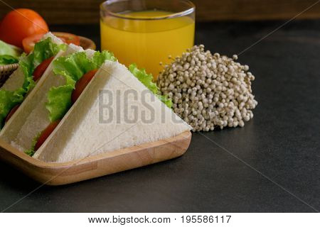Triangle slice piece of sandwich ham cheese with lettuce and tomato on wood plate. Homemade sandwich ham cheese and vegetable for breakfast or lunch. Delicious ham cheese sandwich ready to served on granite table with fresh orange juice.