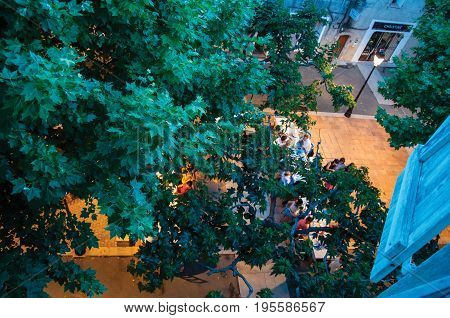 Rians, France - July 08, 2016. People in square restaurant with branches at the early evening, at the lovely village of Rians. Var department, Provence region, southeastern France.