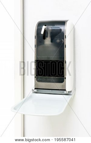 Automatic hand sanitizer dispenser on white wall. Alcohol spray dispenser in public hospital. Vertical image.