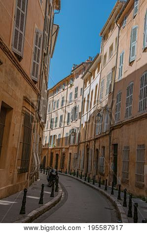 Narrow alley with tall buildings in the shadow in Aix-en-Provence, a pleasant and lively town in the French countryside. Located in Bouches-du-Rhone department, Provence region, southeastern France