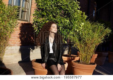 Style and fashion. Beautiful amazing young female with long curly hair wearing black leather jacket and skirt sitting on big plant pot outdoors closing eyes in pleasure enjoying warm sunlight