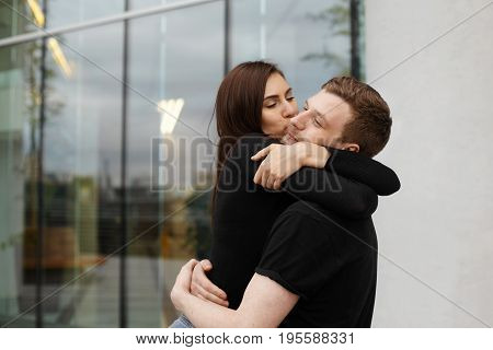 Sweet young European couple hugging against modern glass windows office building background. Outdoor urban shot of charming girl holding tight her attractive boyfriend and kissing him on cheek