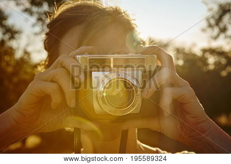 Woman taking pictures with vintage camera. Backlight. Travel background.