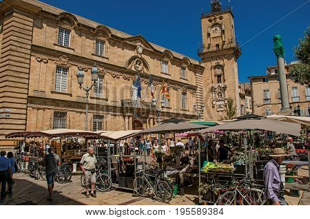 Aix-en-Provence, France - July 09, 2016. Square with market stall, people and clock tower in Aix-en-Provence, a pleasant and lively town in the French countryside. Provence region, southeastern France