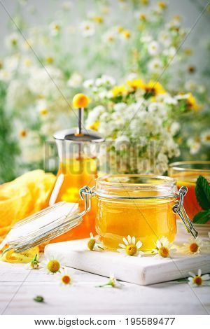 Tasty and healthy honey on white wooden table with flowers of chamomile. Summer still life.