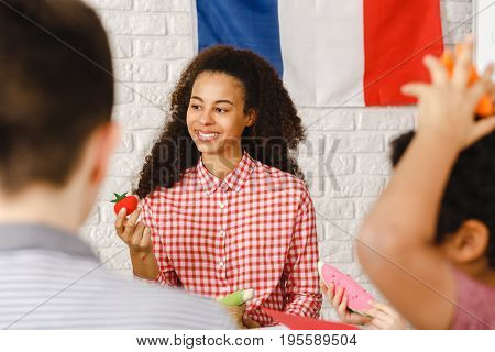 Happy young woman leading french classes with kids
